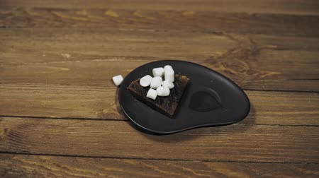 фасонный : Close-up of a black plate with a dark wafer and a white heart-shaped marshmallow on a wooden table. Someone takes a Cup of coffee and starts Breakfast, the camera moves from left to right.