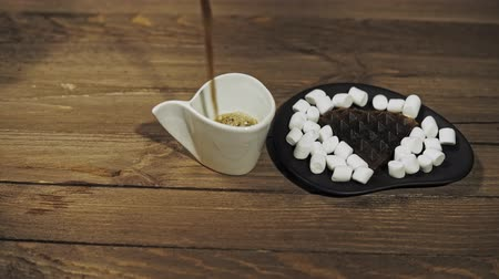 stuffing : Someone serves breakfast pours coffee into a white cup. On a black plate are dark heart waffles with marshmallows, the camera moves from right to left. Stock Footage