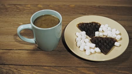 lezzet : Someone sets the table for breakfast pours cream into the coffee into a blue mug. On a beige plate are dark heart waffles with marshmallows, the camera moves from left to right. Stok Video