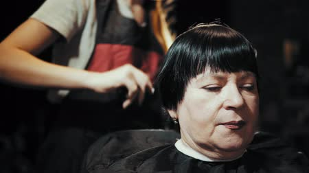 kısa : Mature woman having her hair cut at the hairdressers. Closeup view of a hairdressers hands cutting female dark hair with a thinning shears in beauty salon.