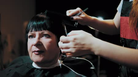 suszarka : Mature woman having her hair cut at the hairdressers. Closeup view of a hairdressers hands cutting female dark hair with a thinning shears in beauty salon.