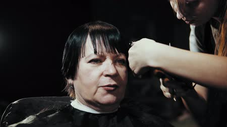 kısa : Mature woman having her hair cut at the hairdressers. Hairdresser trimming female dark hair with scissors in beauty salon.