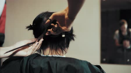 kırpma : Mature woman having her hair cut at the hairdressers. The hairdresser-stylist prepares the female client for a clipping, combs with a brush and clamps the hair with clips.