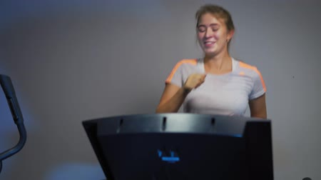 peso : Young blonde woman actively runs on the treadmill in a sport club. Beautiful girl warms up the muscles on the running track before training.