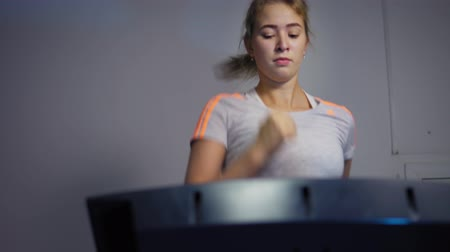 cardiovascolare : Young blonde woman actively runs on the treadmill in a sport club. Beautiful girl warms up the muscles on the running track before training.