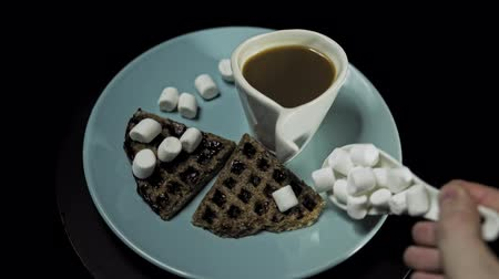 служить : A blue plate with waffles, marshmallows and a white cup of coffee rotates against the hour hand on a black background. Preparation of a romantic breakfast.
