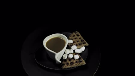 gofret : Top view of a dark plate with waffles, marshmallows and a white cup of coffee rotates against the hour hand on a black background, camera moves away.