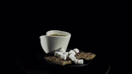 마시멜로 : A dark plate with waffles, marshmallows and a white cup of coffee rotates against the hour hand on a black background, camera is approaching.
