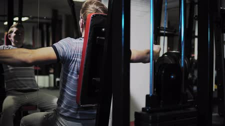 жесткий : Young man develops chest muscles by performing exercises on a power trainer with pectoral deck in sport club, healthy sports lifestyle, fitness concept.