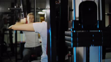 yoğunlaşma : Blonde girl develops the muscles of the chest exercises on the power machine with pectoral deck in the gym. A young woman controls the correctness of the workout in front of a mirror.
