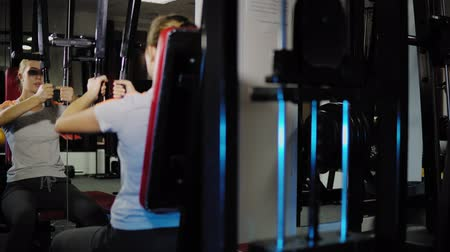 Blonde girl develops the muscles of the chest exercises on the power machine with pectoral deck in the gym. A young woman controls the correctness of the workout in front of a mirror.