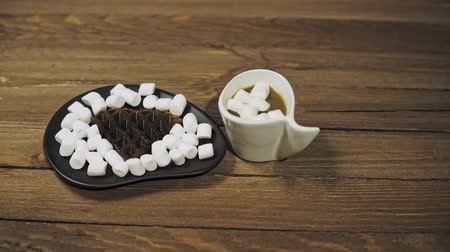 gofret : On a black plate dark heart waffles with marshmallows are on a wooden table. Someone puts coffee in a white cup next to it, the camera moves from right to left. Stok Video
