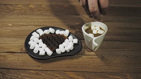 On a black plate dark heart waffles with marshmallows are on a wooden table. Someone pouring marshmallow on coffee in a white cup. The camera moves from left to right. Stok Video