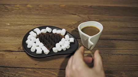 On a black plate dark heart waffles with marshmallows are on a wooden table. Someone puts coffee in a white cup next to it, the camera moves from right to left. Stok Video
