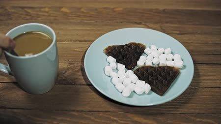 Someone for breakfast mixes cream and coffee in a blue cup. On a azure plate dark heart waffles with marshmallows, the camera moves from right to left.