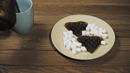 бежевый : Someone sets the table for Breakfast, pouring coffee into a blue mug. On a beige plate are dark heart waffles with marshmallows, the camera moves from right to left.