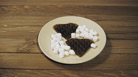 Closeup of baked dark waffles in the shape of a heart with marshmallows on a beige plate on a wooden table, romantic dessert, camera movement from left to right. Stok Video