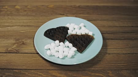 gofret : Closeup of baked dark waffles in the shape of a heart on a blue plate on a wooden table, romantic dessert, camera movement from right to left.