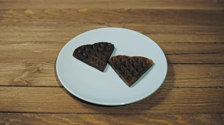 opłatek : Closeup of baked dark waffles in the shape of a heart on a blue plate on a wooden table, romantic dessert, camera movement from right to left.
