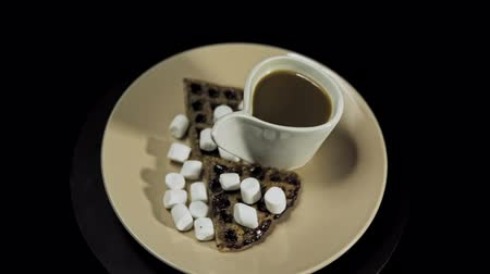 A beige plate with waffles, marshmallows and a white cup of coffee rotates against the hour hand on a black background, camera is approaching.