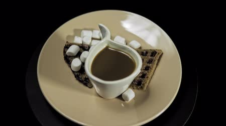 Top view of a beige plate with waffles, marshmallows and a white cup of coffee rotates against the hour hand on a black background, seamless looping.