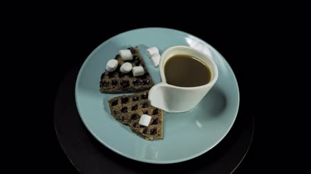 Top view of a blue plate with waffles, marshmallows and a white cup of coffee rotates against the hour hand on a black background, camera is approaching.