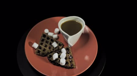 Top view of a red plate with waffles, marshmallows and a white cup of coffee rotates against the hour hand on a black background, camera moves away.