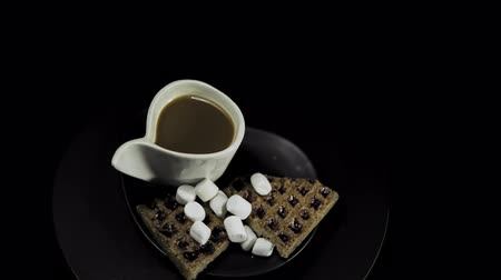 A dark plate with waffles, marshmallows and a white cup of coffee rotates against the hour hand on a black background, seamless looping. Stok Video