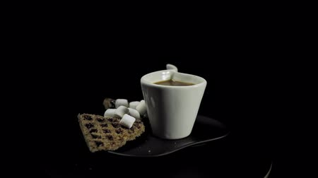 Side view of a dark plate with waffles, marshmallows and a white cup of coffee rotates against the hour hand on a black background, camera moves away. Stok Video