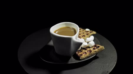 служить : Side view of a dark plate with waffles, marshmallows and a white cup of coffee rotates against the hour hand on a black background. Preparation of a romantic breakfast.