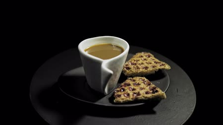 Side view of a dark plate with waffles, marshmallows and a white cup of coffee rotates against the hour hand on a black background, seamless looping.