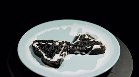 Dark heart-shaped waffles with white sauce lay on a blue plate and turn counterclockwise on a black background. Stok Video