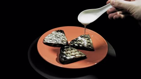 Someone pours white sauce on the dark heart waffles that lie on a coral plate. Preparing for a romantic Breakfast. Stok Video