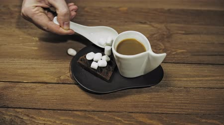 gofret : Close up of someone serves romantic breakfast pouring marshmallow on dark waffles in the shape of a heart, standing next to the coffee cup. The camera moves from left to right.