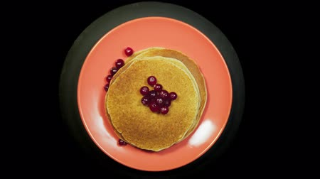 Appetizing stack of pancakes with red berries and sprouts on a coral plate rotates on a black background, top view.