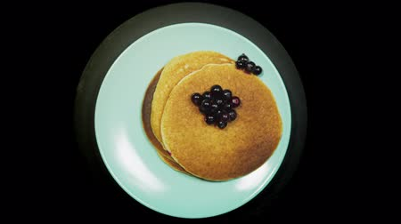Appetizing stack of pancakes with dark berries of blackcurrant on a blue plate rotates on a black background, top view.