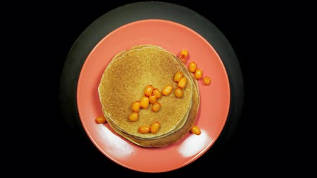 Appetizing stack of pancakes with orange sea-buckthorn berries on a coral plate rotates on a black background, top view.