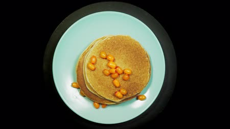 Appetizing stack of pancakes with orange sea-buckthorn berries on a blue plate rotates on a black background, top view.