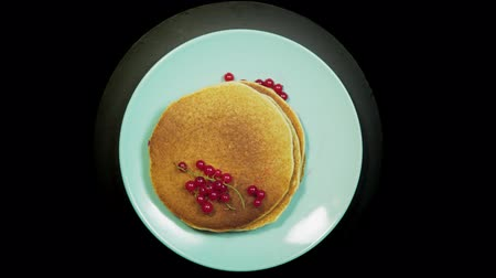 Appetizing stack of pancakes with dark berries of red currant on a blue plate rotates on a black background, top view. Stok Video