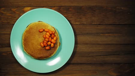 Top view on a azure plate with appetizing pancakes and orange sea-buckthorn berries on a wooden table, hands put a fork and a knife on a dish, the camera moves from right to left. Stok Video