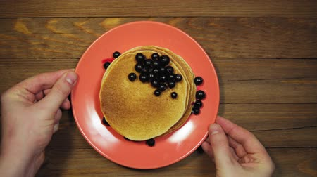 Someone serves a wooden table, hands correcting a coral plate with pancakes and black currant berries, view from above, the camera moves from right to left.