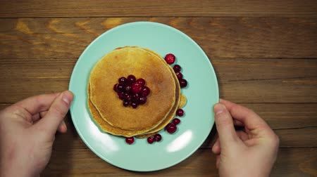 Someone serves a wooden table, hands correcting a azure plate with appetizing pancakes and red cranberries berries, view from above, the camera moves from right to left. Stok Video