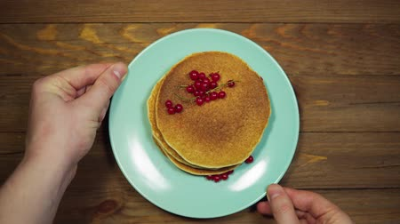 Top view, someone serves a wooden table, hands correcting a azure plate with pancakes and redcurrant berries and put a fork and a knife.