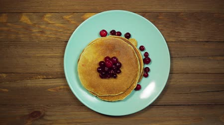 ягода : Top view, someone serves a wooden table, hands correcting a blue plate with pancakes and red cranberries berries and put a fork and a knife. Стоковые видеозаписи