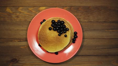 Top view of a wooden table with a coral plate filled with appetizing pancakes and black currants, the camera moves from left to right.