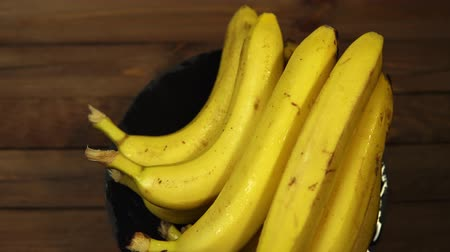 Ripe tasty wet bananas rotate counterclockwise on a black plate on a wooden table.