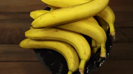 Ripe delicious wet bananas rotate clockwise on a black plate on a wooden table.
