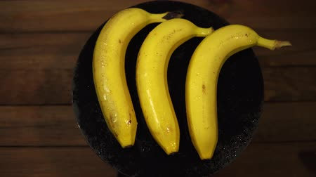 Ripe tasty wet bananas rotate counterclockwise on a black plate on a wooden table, seamless looping.