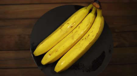 banan : Ripe tasty wet bananas rotate counterclockwise on a black plate on a wooden table, seamless looping.
