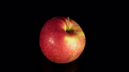 Close-up of a fresh ripe Apple with droplets rotate counterclockwise on a black background, seamless looping.